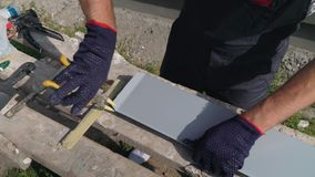 De arbeider dient beschermende handschoenen in voorbereidend pvc-het scherpe metaal van de venstervensterbank met schaarclose-up stock video