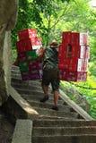De arbeider draagt dozen met dranken Stock Foto