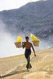 De arbeider draagt een mand met stukken van zwavel stock afbeeldingen