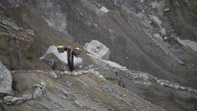 De arbeider draagt zwavel lopend op vulkaankrater stock footage