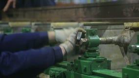 De arbeider draait de noot met een grote moersleutel stock videobeelden