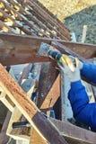 De arbeider in een plaat, een dakrek van het gebouw kan worden gezien stock fotografie