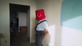 De arbeider in eenvormig met rode emmer op zijn hoofd heeft pret en het dansen stock video