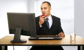 De arbeider eet Snack in Zijn Bureau stock foto's