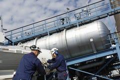De arbeider en de raffinaderij van de olie stock foto