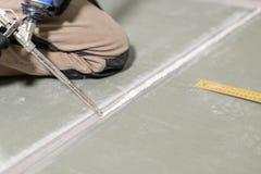 De arbeider gebruikt een polyurethaanschuim voor het lijmen van drywall bij negentig graden Lijm van het het polyurethaan de uitb stock fotografie