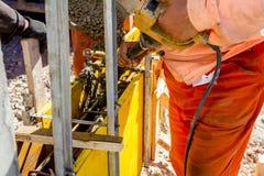 De arbeider gebruikt elektrische trillings aan compact beton in houten stock afbeeldingen