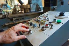 De arbeider gebruikt het controlebord van de CNC machine om het materiaal te verwerken stock afbeeldingen