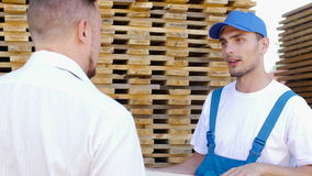 De arbeider, glimlacht en vertelt de koper over verschillende types van hout stock video