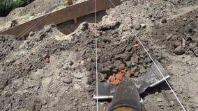De arbeider graaft een schopgeul bij een bouwwerf Lay-outstichting met een strakke kabel voor het nauwkeurige graven stock videobeelden