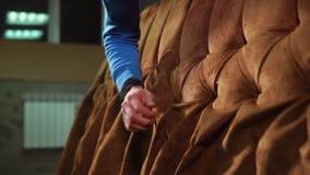 De arbeider haalt een stof op een karkas van bank, close-up aan stock video