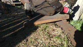 De arbeider in handschoenen snijdt metaalplaat in twee delen door schuurmachine, het huiswerk, stock video