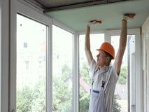 De arbeider heft en duwt drywall op stock footage