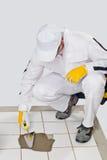 De arbeider herstelt oude witte tegels met tegelkleefstof Stock Foto