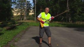 De arbeider imiteert een gitaarspel tijdens het werk stock videobeelden
