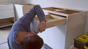 De arbeider installeert lade aan de keuken van de keukenkastbouw stock videobeelden