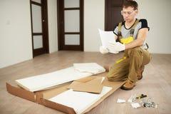 De arbeider installeert meubilair met instructie royalty-vrije stock fotografie
