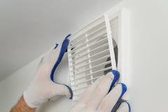 De arbeider installeert ventilatietraliewerk Royalty-vrije Stock Afbeeldingen