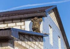 De arbeider isoleert de muren van het huis met plastic panelen royalty-vrije stock afbeeldingen