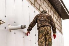 De arbeider isoleert de muren van het huis met plastic panelen stock foto's