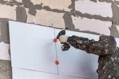 De arbeider isoleert de muren van het huis met plastic panelen royalty-vrije stock afbeelding