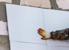 De arbeider isoleert de muren van het huis met plastic panelen stock foto