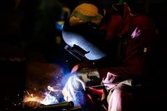 De arbeider is lasplaat door het booglassen van het schildmetaal Stock Foto's
