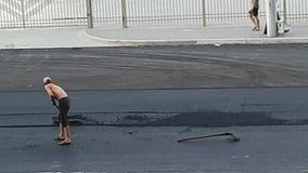 De arbeider legt met de hand asfalt Reparatie van de weg stock footage