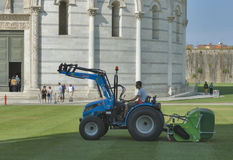 De arbeider maait het gras voor Baptistery in Pisa Stock Fotografie