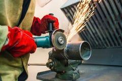 de arbeider maakt een gelaste naad op een sectie van een staalpijp met behulp van schoon een malende machine royalty-vrije stock fotografie