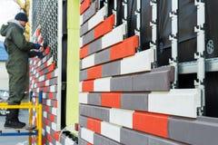 De arbeider maakt het onder ogen zien en het verwarmen van de muur door een kunstmatige decoratieve steen stock foto