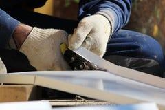 De arbeider maakt het sladding van vensters in het herstelde gebouw in de stad, snijdt het metaalblad voor de helling met schaar royalty-vrije stock foto