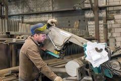 De arbeider maakt het zagen van het metaalwerkstuk op een lintzaag stock afbeelding