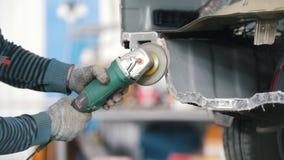 De arbeider maalt de besnoeiing op de auto De dienst van de autoreparatie stock footage