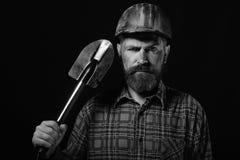 De arbeider met brutaal beeld draagt vuile helm en houdt schop royalty-vrije stock foto