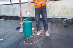 De arbeider, met een toorts van het dakwerkgas, installeert broodjes van bitumineus waterdicht makend membraan op een terras - da royalty-vrije stock foto