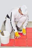 De arbeider met emmerkleefstof past rode tegels toe Stock Foto