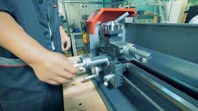 De arbeider met kunstmatige handen, sluit omhoog De mens met prothetische handen werkt bij een installatie, draaiend een handvat
