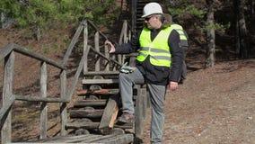 De arbeider neemt beeld dichtbij op tabletpc aan het gebroken houten spoor stock videobeelden