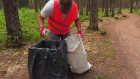 De arbeider neemt plastic flessen van afvalbak stock video