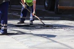 De arbeider nivelleert de kruimel van asfalt in de kuil met een belemmering-rol vóór het bedekken met een weg mini de bouwrol Stock Afbeeldingen