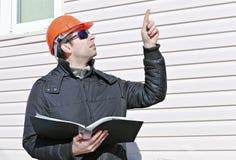 De arbeider op een bouwwerf in de winter bekijkt de tekening en toont vinger Stock Foto's