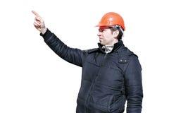 De arbeider op een bouwwerf in de winter leidt en hand het gesticuleren stock foto's