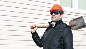 De arbeider in oranje bouwvakker en zonnebril met schop in zijn hand Royalty-vrije Stock Foto