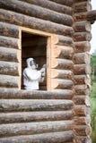 De arbeider in overall en volledig gezichtsmasker maalt een venster openend in een vers gelegd logboekhuis stock foto