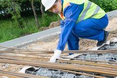 De arbeider in overall neemt ijzerstaven voor bouw, close-up stock foto