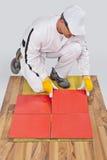 De arbeider past ceramiektegels toe Stock Afbeelding