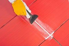 De arbeider past pleisterwhit rubbertroffel rode tegels toe Stock Fotografie