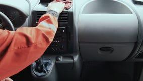 De arbeider past poetsmiddel op dashboardpaneel van toe auto stock videobeelden