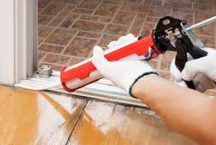 De arbeider past silicone toe waterdicht maakt op de vloer voor overzees stock foto's